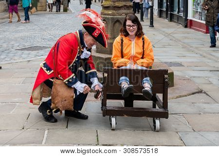 Chester, Uk - 26th June 2019: The Town Crier Locks Up A Tourist In A Stockade In The Middle Of The C