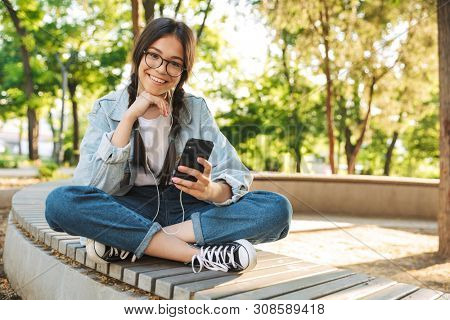 Photo of a pleased positive happy cute young student girl wearing eyeglasses sitting on bench outdoors in nature park using mobile phone chatting listening music with earphones.