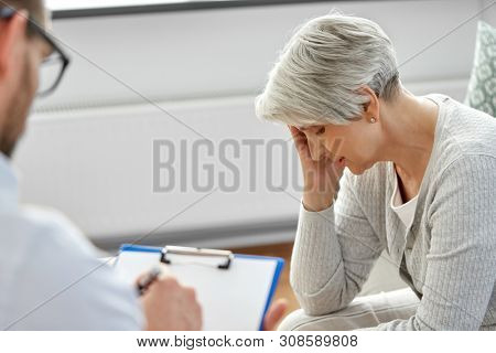 geriatric psychology, mental therapy and old age concept - sad unhappy senior woman patient and psychologist with clipboard taking notes at psychotherapy session