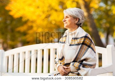 old age, retirement and people concept - portrait of happy senior woman at autumn park