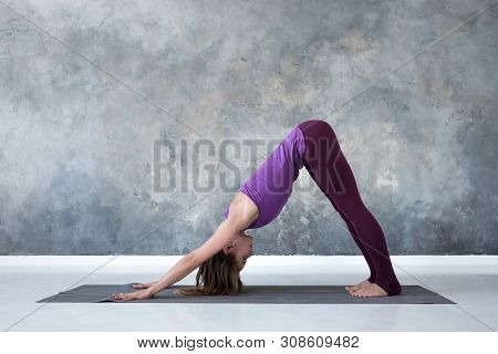 Woman Doing Yoga Exercise Downward Facing Dog Pose Or Adho Mukha Svanasana.