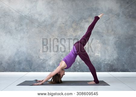 Woman Doing Yoga Variation Of Downward Facing Dog Pose Or Adho Mukha Svanasana.