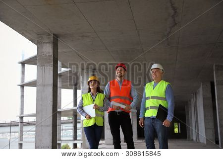 Professional Builder And Foreman In Safety Equipment At Construction Site