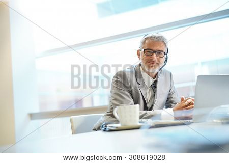 Mature businessman looking at camera with headpiece