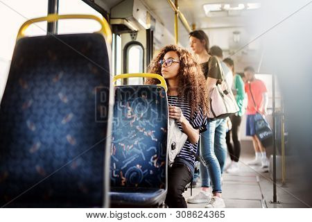 Young Pretty Woman Is Sitting On A Bus Seat And Looking Through The Window While Holding Her Bag On