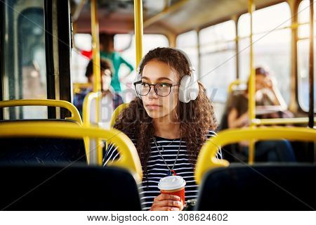A Cute Beautiful Young Woman With Curly Hair Is Sitting In The Bus Seat Listening To Music Drinking