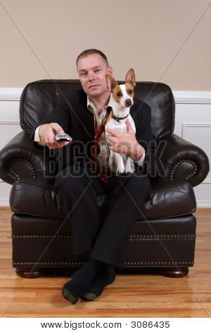 A man relaxing with his dog and remote control after a long day at work. poster