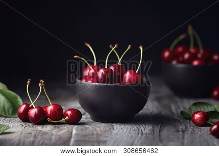 Ripe red cherries in a bowl and next to it on wooden table.