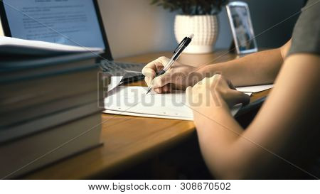 College Or University Student Doing School Homework At Home. Working Late At Night. Young Woman Writ