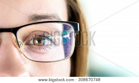 Close Up Of Eye And Woman Wearing Glasses. Optometry, Myopia Or Laser Surgery Concept. Brown Eyed Gi
