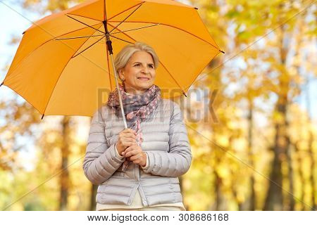 old age, weather and season concept - portrait of happy senior woman with umbrella at autumn park