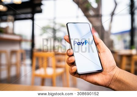 Chiang Mai, Thailand - Mar. 23,2019: Man Holding Xiaomi Mi Mix 3 With Paypal Apps On The Screen. Pay