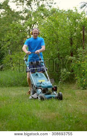 The Man With Headphones Mows A Lawn With The Petrol Lawn-mower In The Warm Summer
