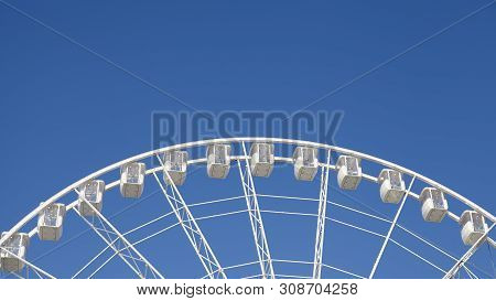 Panoramic View Of A Ferris Wheel Against The Blue Sky.