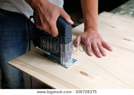 Carpenter Is Sawing A Plywood Sheet With Electric Jig Saw Machine In Carpentry Workshop. Close Up Ha