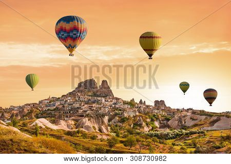 Colorful Hot Air Balloons Flying Over The Valley At Cappadocia, Uchisar, Turkey. Volcanic Mountains
