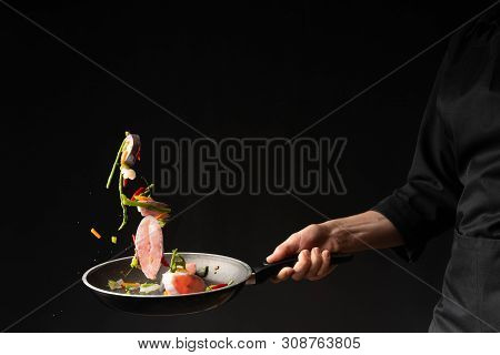 Close-up. Chef Cook Fry Fish With Vegetables On A Griddle On A Black Background. Horizontal Photo. S