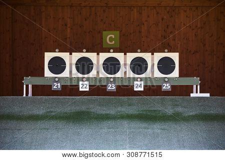 Bullseye Target With Bullet Holes In Center, Close-up. Gun Shooting Range