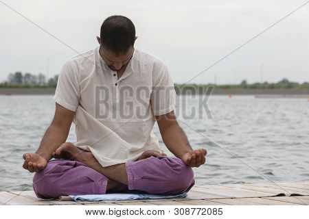 Young Man Doing Yoga And Meditating In Warrior Pose On Beach