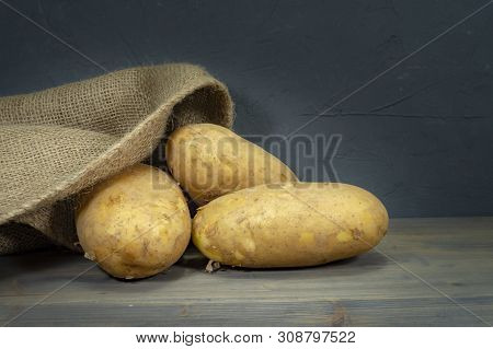 Raw, Unwashed, Unpeeled Potatoes, Spilling Out Of Hessian Sack On A Rustic Old Wooden Background