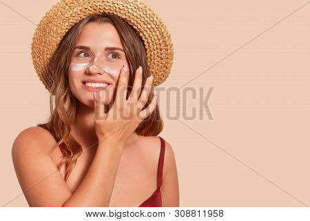 Photo Of Attractive Smiling Woman With Long Hair, Has Happy Facial Expression, Applaying Sunscreen,