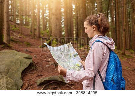 Attractive Energetic Young Lady Holding Map In Both Hands, Looking Attentively At Map, Getting Lost