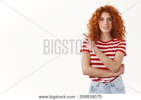 Girl Asking Friend If She Already Saw Awesome Promo. Attactive Redhead Curly Woman Pointing Upper Le