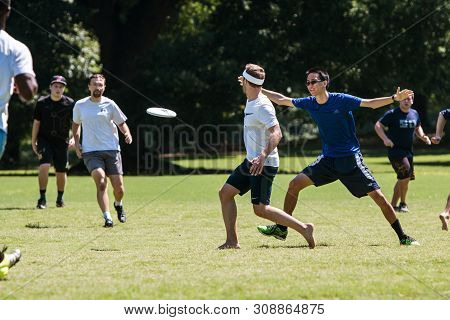Atlanta, Ga - July 28:  A Man Tosses A Frisbee To A Teammate In An Ultimate Frisbee Game In Piedmont