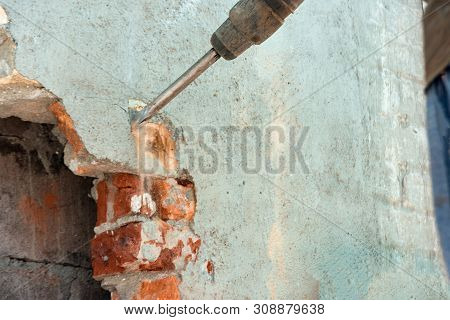 Disassembly Of Walls And Openings With An Electric Jackhammer, Close-up, Dust Hoarse From Under The