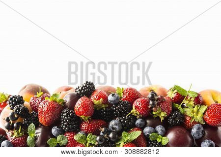 Mix Berries And Fruits On White Background. Ripe Blackberries, Strawberries, Blackcurrants And Plums