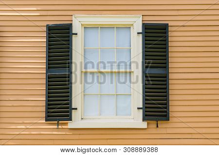 Detail Of Historic Double Hung Window With Black Shutters On A Historic Home In New England