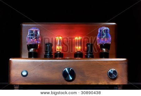 Old-fashioned electronic device amplifier with glowing bulb diode lamp for sound reproduction over dark background