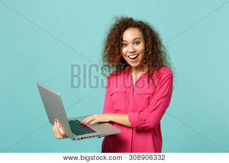 Portrait Of Excited African Girl In Pink Casual Clothes Using Laptop Pc Computer Isolated On Blue Tu