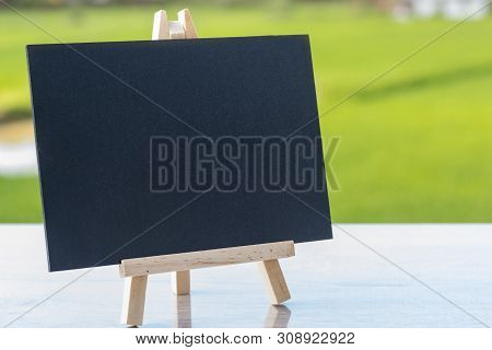 Image Of Empty Small Chalkboard On Wooden Easel For Notes Over Wooden Table Outdoor With Blurred Nat