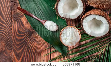 Top View Of Coconut Mct Oil In Bowl And In Spoon And Halved Coco-nut On Wooden Table. Health Benefit