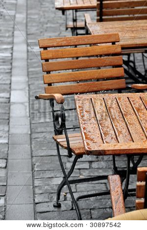Wet chair and table in street cafe