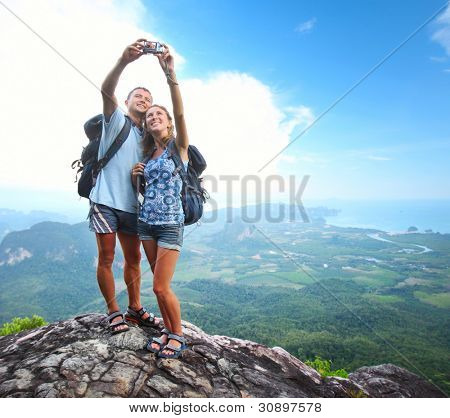 Happy couple with backpacks making a snapshot of themselves on top of a mountain