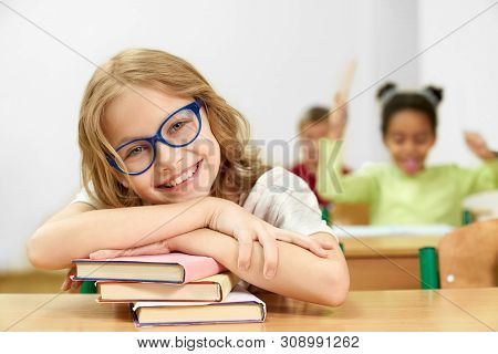 Cheerful Child Posing While Sitting At Desk And Lying On Books In Classroom. Happy Girl Wearing Glas