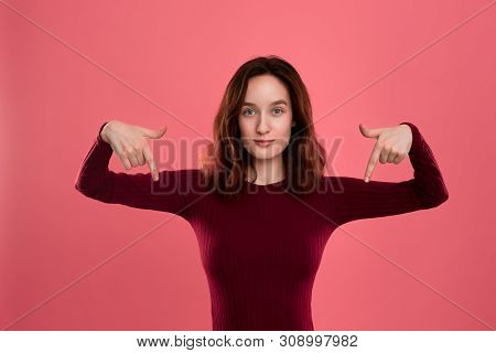 Excited Young Lady Standing Isolated Over Dark Pink Background Pointing Down With Fingers. Place For