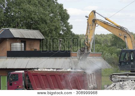 Excavator Loads Construction Waste Into A Red Truck. Destroyed Concrete, Construction Waste. The Roa