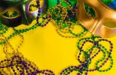 Two Mardi Gras mask with colorful beads on a yellow background poster