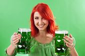 Photo of a beautiful redhead holding two huge mugs of green beer for St. Patricks Day celebrations. poster