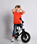 Shocked kid boy on bicycle with grabbed his head like he feels adrenaline of very high speed or extreme jump he has done on white background poster
