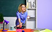 Happy teacher in classroom. Young female teacher. Young teacher in glasses over green chalkboard. Teacher with marker. poster