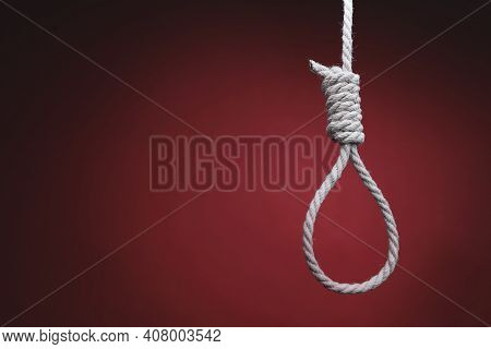 Rope In Shape Of Gallows Hangs On Red Background. Concept Of Depression, Hopelessness, And Suicide.