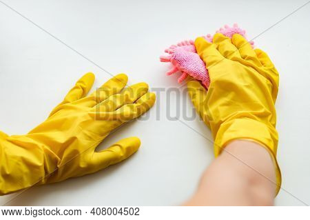 A Female Hand In A Yellow Rubber Glove With A Pink Microfiber Rag Washes And Polishes The White Surf