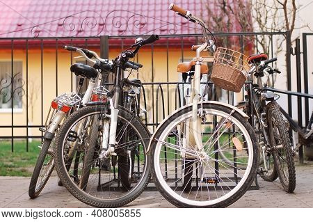 City And Mountain Bikes Are Parked In A Bicycle Parking Lot In The City. Horizontal
