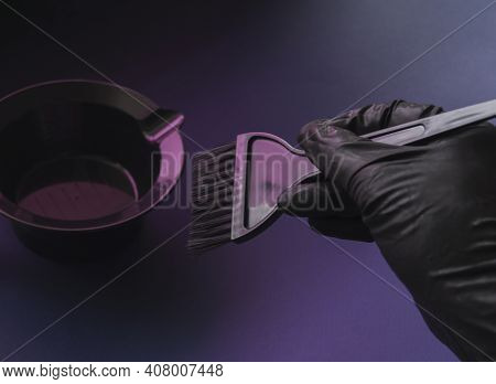 A Gloved Hand Holds A Hair Dye Brush. Futuristic Hair Salon Background In Purple Neon Light, Trendy