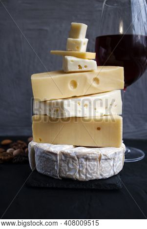 Assortment Of Different Cheese Types On Dark And White Background. Different Types Of Delicious Chee