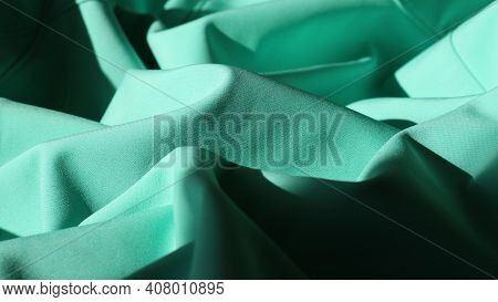 Emerald Dense Fabric Is Folded With Graceful Curves, Dark Waves In The Glow Of Sunlight, Elegant Dra